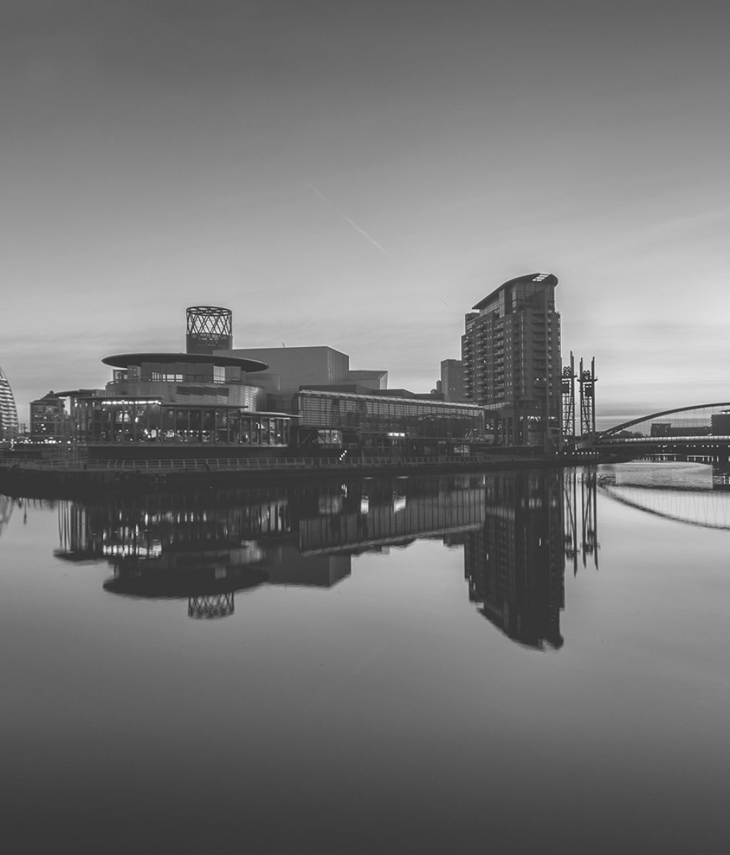 Orange sunrise at Salford Quays with blue sky and clear reflecti